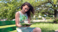 Absorbed girl sitting in the park and making notes in her journal Stock Footage