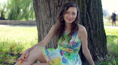 Pretty girl in floral dress sitting next to the tree and smiling to the camera Stock Footage