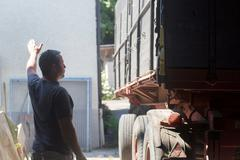 Male farmer guiding trailer into barn Stock Photos