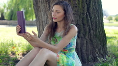 Pretty girl in floral dress doing selfies on tablet while sitting in the park Stock Footage