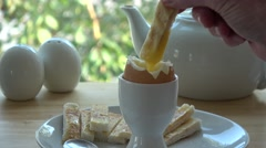 Toasted soldiers being dipped into a boiled egg, breakfast table Stock Footage