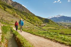 Mature couple hiking along country road, Meran, South Tyrol, Italy Stock Photos