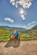 Mature couple sitting by roadside, looking at view, rear view, Meran, South Stock Photos