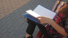 Young business woman lists blank documents on the sun lit street Stock Footage