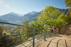 Mature couple sitting on bench, looking at view, Meran, South Tyrol, Italy Stock Photos