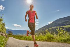 Young woman running along rural road, Meran, South Tyrol, Italy Stock Photos
