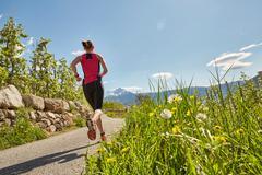Young woman running along rural road, rear view, Meran, South Tyrol, Italy Stock Photos