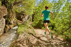Young woman running along rural pathway, rear view, Meran, South Tyrol, Italy Stock Photos