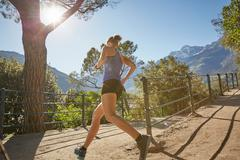 Young woman running along rural pathway, Meran, South Tyrol, Italy Stock Photos