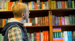Pensive student looking thoughtful while standing next to the bookshelves Stock Footage