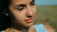 Young beautiful girl in a blue dress enjoys flowers steppe. A young woman in a Stock Footage