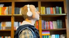 Student standing next to the bookshelves and listening music on headphones Stock Footage