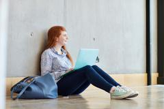 Young female student sitting on floor with laptop at higher education college Stock Photos