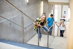 Young female student sliding down stairway handrail at higher education college Stock Photos