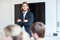 Portrait of male lecturer with arms folded in higher education college classroom Stock Photos