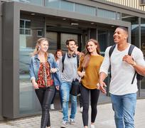 Group of male and female students leaving higher education college Stock Photos