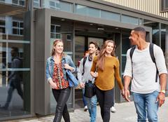 Male and female students leaving higher education college Stock Photos