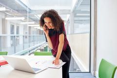 Female designer reading laptop and talking on smartphone in design studio Stock Photos