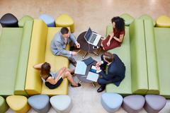 Overhead view of businessmen and businesswomen meeting on design studio sofas Stock Photos