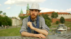 Tourist sitting next to the castle and looking very worried Stock Footage