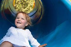 Female toddler sliding down tube slide, Sagres, Algarve, Portugal Stock Photos