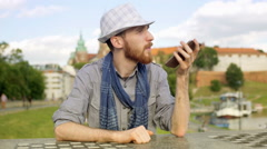 Tourist speaking on loudspeaker while sitting by the castle Stock Footage