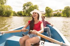 Happy young couple rowing a boat in Regents Park, London, UK Stock Photos