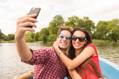 Young couple taking smartphone selfie in rowing boat in Regents Park, London, UK Stock Photos