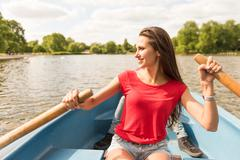 Young woman and boyfriend in rowing boat in Regents Park, London, UK Stock Photos