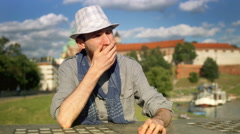 Tourist looking aroud and yawning while sitting next to the castle Stock Footage