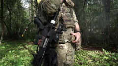 An armed soldier with a rifle and military uniform standing in the woods and Stock Footage