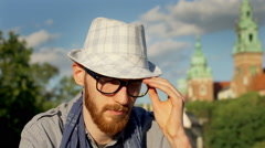 Man looking worried while sitting at sunny dat outside Stock Footage