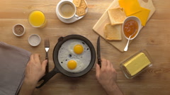 Male hands cut the fried eggs on black pan, top view Stock Footage