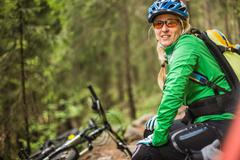 Woman mountain biker looking at camera smiling, Meran, South Tyrol, Italy Stock Photos