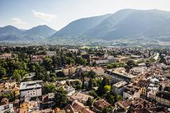 Buildings by tree covered mountains, Meran, South Tyrol, Italy Stock Photos