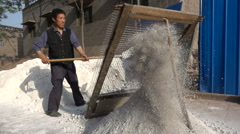Slow motion of construction worker filtering cement in village China Stock Footage