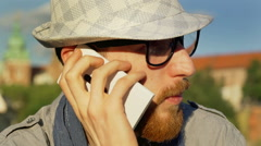 Man chatting on cellphone and looking happy while sitting outside Stock Footage