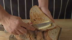 Chef hand rubs butter on piece of rye bread Stock Footage