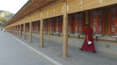 Steadycam shot of a monk walking past prayer wheels in Xiahe, China Stock Footage