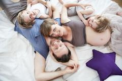 Pregnant mother with family, lying on bed Stock Photos