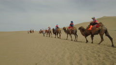Tourists ride camels through the desert landscapes near Dunhuang in China Stock Footage