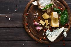 Cheese delikatessen on rustic wood, blue roquefort, brie and parmesan Stock Photos