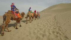 China tourism, people ride camels through Dunhuang sand dune mountains Stock Footage