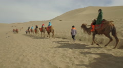 China travel recreation, tourists ride camels in desert landscape Dunhuang Stock Footage
