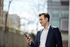 Businessman reading smartphone texts outside office, London, UK Stock Photos