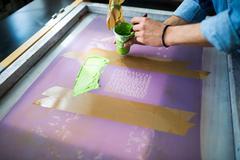 Hands of male printer applying green ink to silkscreen in printing press studio Stock Photos