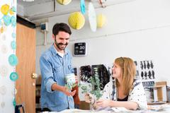 Female and male designer laughing at twig leaves in printing press studio Stock Photos