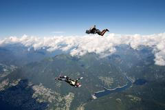 Freestyle skydiving team training together. One man performing air-ballet, Stock Photos