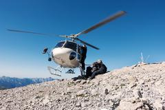 BASE jumping team exiting helicopter on top of mountain, Italian Alps, Alleghe, Stock Photos