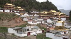 Golden color roofs on Tibetan monastery in mountains Langmusi Stock Footage